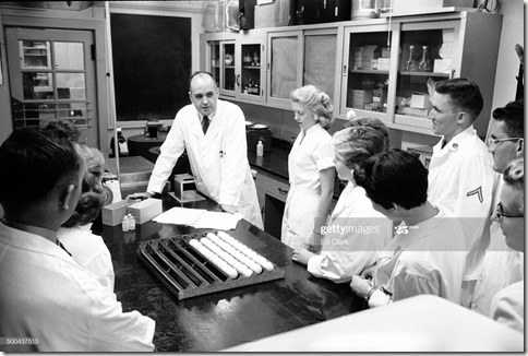 American microbiologist Dr Maurice Hilleman (1919 - 2005) (center, rear) talks with his research team as they study the flu virus in a lab at Walter Reed Army Institute of Research, Silver Springs, Maryland, 1957. Fellow microbiologist F Joseph Flatley is near left. (Photo by Ed Clark/The LIFE Picture Collection via Getty Images)